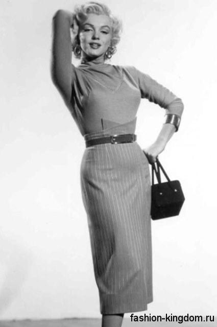 Мэрилин Монро в юбке-карандаш серого цвета с вертикальным полосатым принтом, которая сочетается с кофточкой серого тона с рукавами три четверти и маленькой сумочкой черной расцветки.