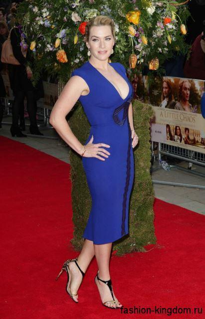 Обладательница типа фигуры яблоко Кейт Уинслет в коктейльном платье-футляр темно-синего оттенка с черными вставками, длиной ниже колен, с глубоким декольте и без рукавов. Дополняют образ босоножки золотисто-черного тона на высоком каблуке.