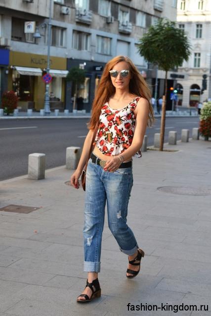 Укороченные джинсы бойфренды с потертостями, светло-синего цвета в сочетании с топом белого тона с красным рисунком и черными босоножками на низком каблуке.