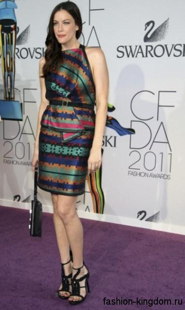 Обладательница фигуры «О» Лив Тайлер в атласном разноцветном платье с баской, длиной выше колен, без рукавов, которое сочетается с клатчем черного тона и босоножками черного цвета на высоком каблуке.