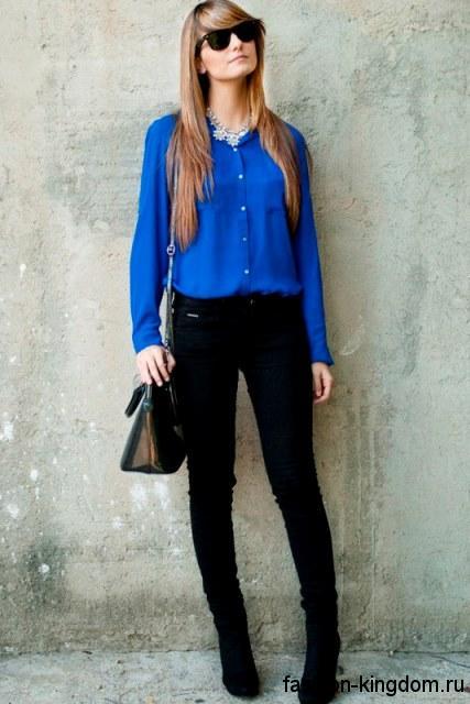 Джинсы черного цвета зауженного фасона в сочетании с блузкой королевского синего оттенка с длинными рукавами.