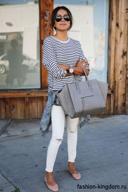 Узкие белые джинсы с прорезями гармонируют со свитером черно-белого тона в полоску свободного силуэта, большой серой сумочкой и бежевыми балетками.