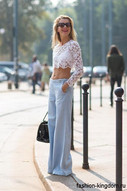 Женские джинсы клеш небесно-голубого цвета гармонируют с ажурной короткой блузкой белого тона и большой черной сумочкой.