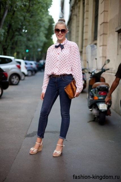 Синие джинсы укороченного фасона, с завышенной талией гармонируют с белой блузкой в красный горошек и босоножками белого цвета.