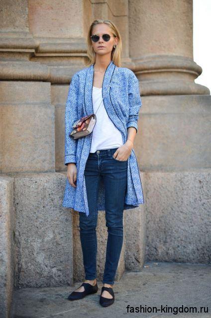 Узкие джинсы синего цвета гармонируют с белым топом, удлиненным кардиганом светло-синего оттенка и черными туфлями на низком ходу.