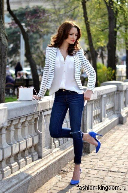 Джинсы скинни темно-синего цвета сочетаются с белой шифоновой блузкой, коротким жакетом черно-белой расцветки в полоску и туфлями синего тона на высоком каблуке.
