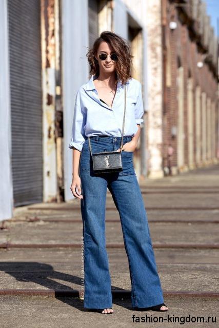 Джинсы клеш светло-синего цвета с высокой талией сочетаются с рубашкой бледно-голубого оттенка и босоножками черного тона на каблуке.