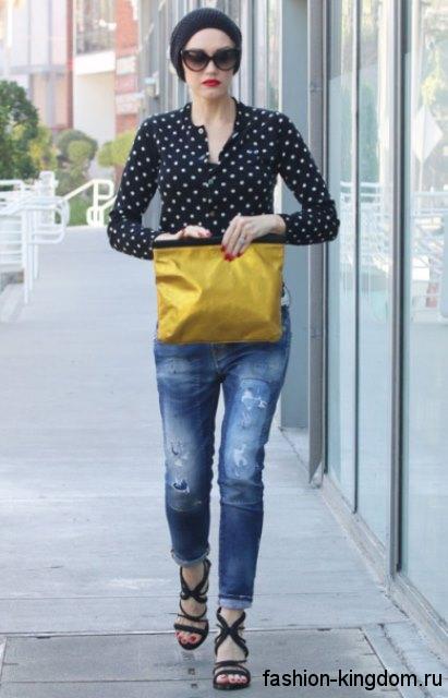 Модные джинсы бойфренды с потертостями, синего цвета в сочетании с рубашкой черного тона в белый горох и черными босоножками на каблуке.