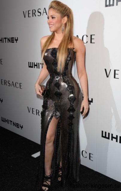 Обладательница типа фигуры груша Шакира в вечернем платье серебристого оттенка, длиной в пол, с высоким разрезом, корсетным верхом и кожаными вставками, которое сочетается с босоножками черного цвета на высоком каблуке.