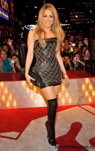 Шакира в платье-мини черно-серебристой расцветки, приталенного фасона, без рукавов, которое сочетается с кожаным клатчем черного тона и высокими сапогами черного цвета на каблуке.