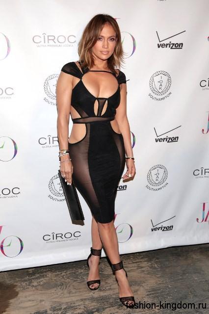 Дженнифер Лопес в полупрозрачном платье черного цвета, приталенного силуэта, длиной до колен, которое сочетается с клатчем черного тона и открытыми черными босоножками на каблуке.
