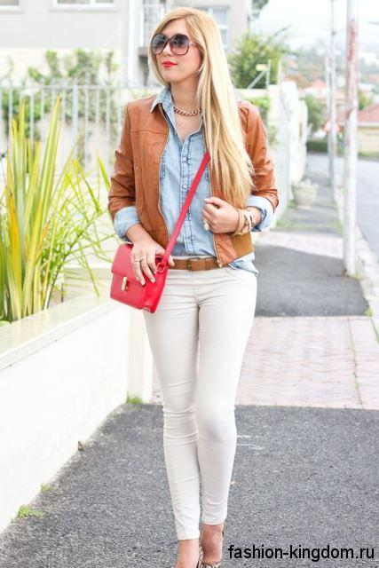 Узкие белые джинсы гармонируют с джинсовой рубашкой, короткой кожаной курткой светло-коричневого оттенка и сумочкой малинового цвета.