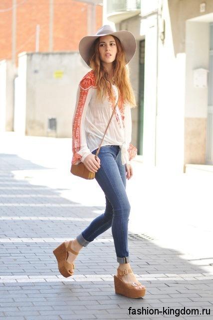 Узкие джинсы синего цвета сочетаются с шифоновой блузкой бело-красной расцветки свободного силуэта, сумочкой и босоножками на платформе коричневого тона.