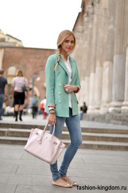 Джинсы зауженного фасона синего цвета сочетаются с белой блузкой, коротким пальто светло-бирюзового оттенка и золотистыми балетками.