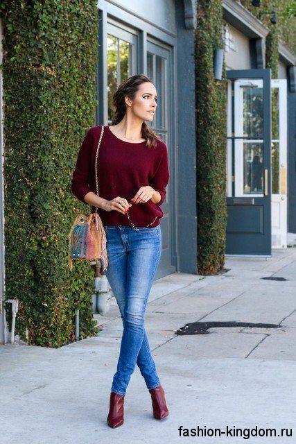 Повседневный образ с джинсами скинни светло-синего цвета, свитером бордового оттенка, коричневой сумочкой и ботильонами цвета марсала на каблуке.