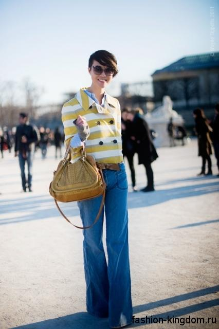 Модные джинсы клеш синего цвета в тандеме с коротким жакетом желто-белой расцветки в полоску и дамской сумочкой горчичного оттенка.