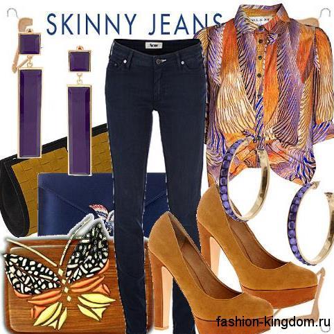 Женские джинсы темно-синего цвета зауженного силуэта в тандеме с короткой блузкой рыже-фиолетовой расцветки с абстрактным принтом и коричневыми туфлями на каблуке.
