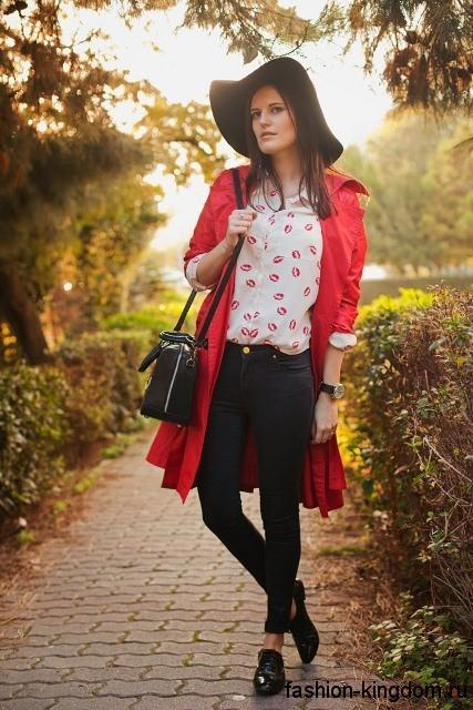 Узкие джинсы черного цвета в тандеме с бежевой блузкой с принтом, плащом ярко-красного оттенка длиной до колен и черными аксессуарами.