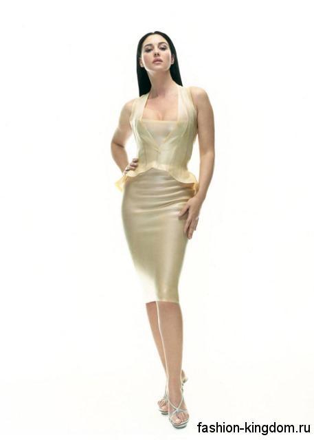 Моника Беллучи в шикарном платье-футляр кремового оттенка, длиной до колен, без рукавов декорированном баской, которое сочетается с открытыми босоножками серебристого цвета на высоком каблуке.