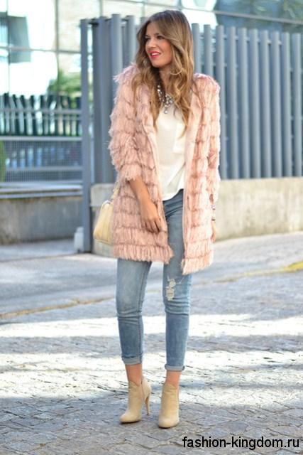 Укороченные джинсы фасона скинни, голубого цвета, с потертостями дополнят образ в сочетании с белой блузкой, меховым пальто розового оттенка с рукавами три четверти и ботильонами молочного тона на каблуке.