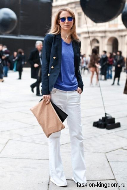 Женские джинсы клеш белого цвета в сочетании с синим топом, пиджаком черного тона и бежевой сумкой-конверт.