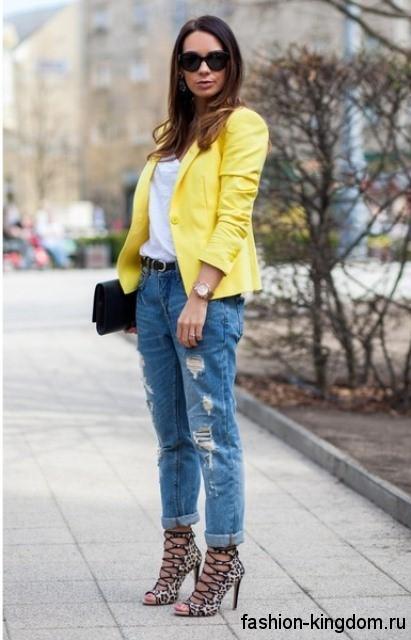 Женские джинсы бойфренды синего цвета с прорезями гармонируют с белым топом, коротким пиджаком ярко-желтого тона, черным клатчем и босоножками леопардовой расцветки на каблуке.