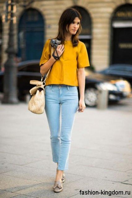 Узкие джинсы голубого цвета гармонируют с блузкой горчичного оттенка с короткими рукавами, свободного фасона и серебристыми туфлями на низком ходу.