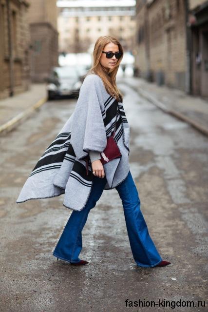Джинсы клеш синего цвета гармонируют с удлиненным пончо черно-серой расцветки, асимметричного кроя и бордовыми туфлями на каблуке.