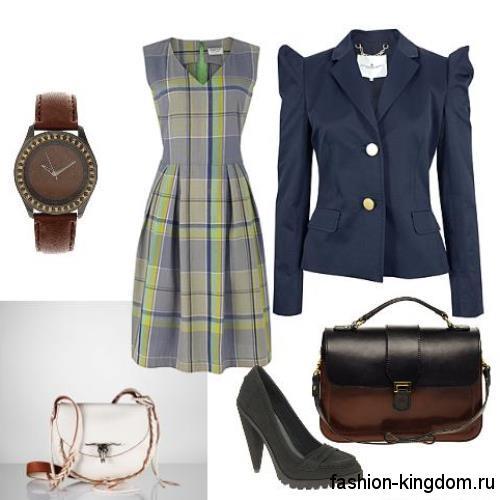 Платье серо-зеленой расцветки в клетку, полуприталенного кроя, без рукавов для офисного стиля в тандеме с пиджаком полуночно-синего оттенка, сумочкой черно-коричневого тона и туфлями черного цвета на каблуке.