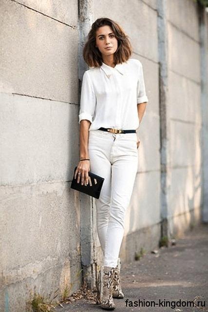 Джинсы белого цвета с завышенной талией сочетаются с блузкой белого тона с рукавами до локтя и ботильонами змеиной расцветки на каблуке.