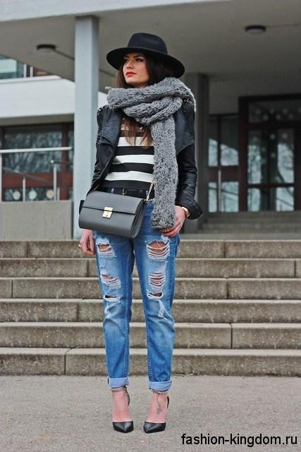 Джинсы синего цвета с прорезями гармонично смотрятся с кожаной черной курткой, серой сумочкой и открытыми туфлями черного тона на каблуке.
