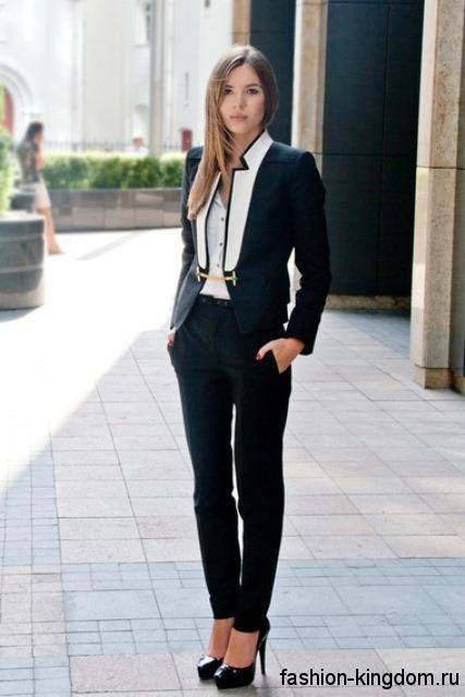 Черные узкие джинсы для офисного стиля гармонируют с белой блузкой, приталенным пиджаком черно-белой расцветки и туфлями черного тона на каблуке.