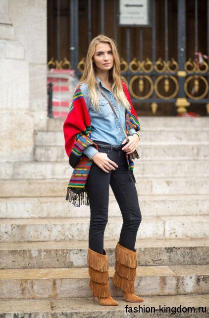 Зауженные черные джинсы гармонируют со светло-голубой джинсовой рубашкой, палантином красного тона и высокими сапогами светло-коричневой расцветки с бахромой и на каблуке.