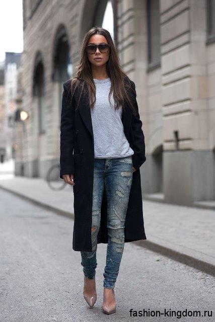 Узкие джинсы светло-синего цвета с потертостями в тандеме с кофточкой серого тона, демисезонным черным пальто длиной ниже колен и туфлями бежевой расцветки на каблуке.