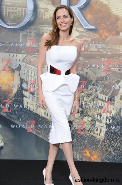 Анджелина Джоли в коктейльном платье белого цвета, приталенного силуэта, с широкой баской и без рукавов, которое сочетается с классическими туфлями белого тона на высоком каблуке.