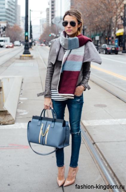 Синие узкие джинсы с прорезями создадут осенний образ в сочетании с кожаной курткой серого цвета, широким шарфом, большой синей сумкой и туфлями бежевого оттенка на каблуке.