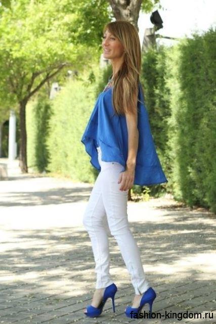Белые летние джинсы зауженного фасона дополнятся шифоновой синей блузкой асимметричного кроя, без рукавов и открытыми туфлями синего цвета на каблуке.