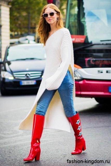 Женские джинсы светло-синего цвета прямого фасона дополняются длинным вязаным кардиганом белого тона, асимметричного кроя и высокими красными сапогами на широком каблуке.