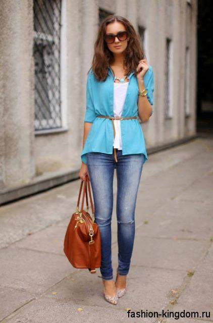 Узкие синие джинсы гармонично смотрятся с белым топом, тонкой рубашкой голубого цвета, большой рыжей сумкой и серебристыми туфлями на высоком каблуке.