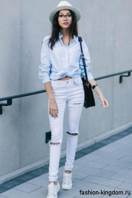 Летний образ с узкими джинсами белого цвета с прорезями и высокой талией, рубашкой светло-голубого оттенка, черной сумочкой и белыми кроссовками.