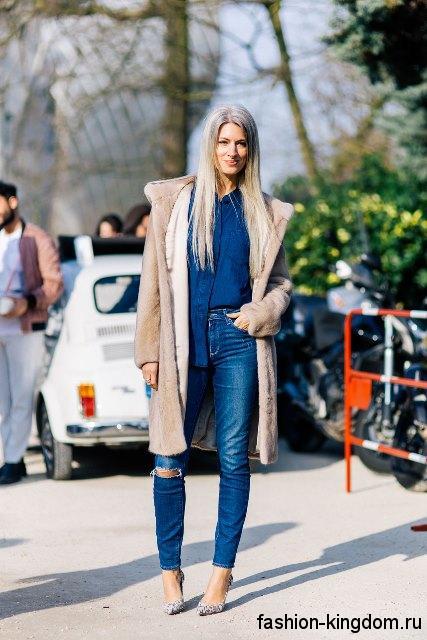 Осенний образ с узкими джинсами синего цвета с прорезями, рубашкой темно-синего оттенка, меховым пальто бежевого тона и серебристыми туфлями на каблуке.