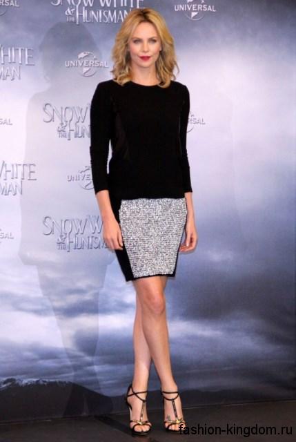 Шарлиз Терон в тонком свитере черного цвета полуприталенного силуэта, короткой юбке черно-серой расцветки прямого фасона и открытых босоножках на высоком каблуке.