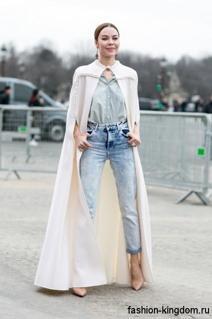 Укороченные джинсы светло-синего цвета с высокой талией в тандеме с блузкой серо-голубого оттенка, длинным пальто-кейп белого тона и бежевыми туфлями на каблуке.
