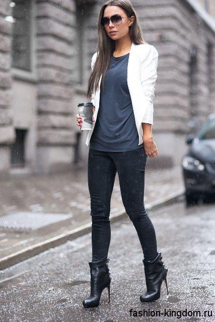 Черные джинсы зауженного фасона сочетаются с топом темно-серого тона, коротким белым пиджаком и кожаным черными ботильонами на каблуке.
