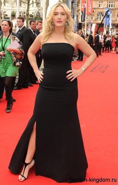 Кейт Уинслет в элегантном вечернем платье черного цвета, полуприталенного силуэта, длиной в пол, с разрезом до колена, которое сочетается с босоножками черного тона на высоком каблуке.