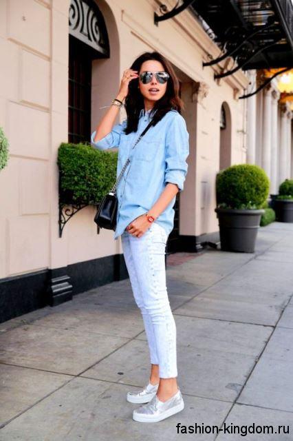 Джинсы скинни белого цвета на летний период сочетаются с джинсовой рубашкой голубого тона и маленькой черной сумочкой.