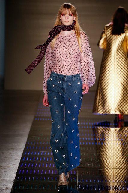 Летние джинсы клеш синего цвета, декорированные металлическими вставками, с высокой талией в тандеме с розовой шифоновой блузкой с длинными рукавами от Au Jour Le Jour.