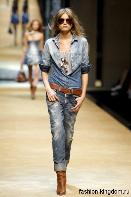 Синие джинсы бойфренды с потертостями и прорезями в тандеме с джинсовой рубашкой синего цвета с рукавами три четверти и сапогами рыжего тона на каблуке от Dolce& Gabbana.