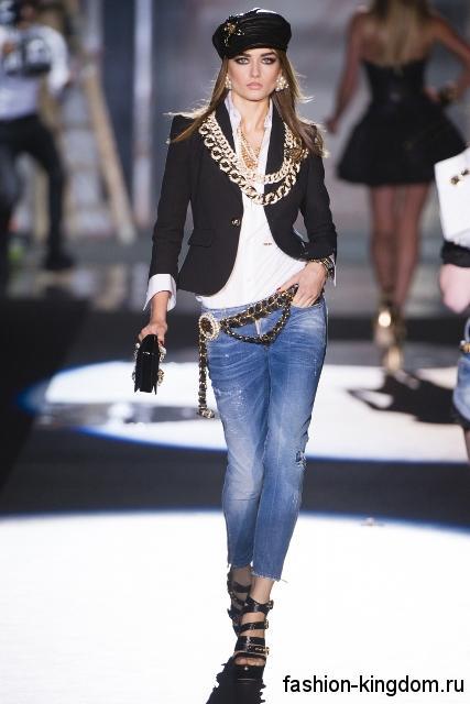Укороченные синие джинсы из коллекции Dsquared² гармонируют с белой блузкой, коротким черным пиджаком, массивными золотистыми украшениями, черными босоножками и аксессуарами.
