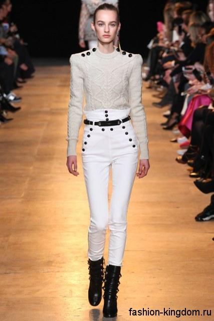 Стильные белые джинсы с высокой талией, зауженного силуэта, декорированные черными пуговицами и поясом, в тандеме с вязаным свитером белого тона и короткими сапогами черного цвета на каблуке от ISABEL MARANT.